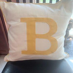 Yellow letter B decorative pillow.